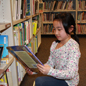 Student looking at book next to library shelf